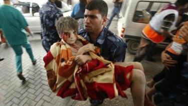 A Palestinian policeman carries a boy, who medics said was wounded in Israeli shelling, at a hospital in Gaza City on Sunday.