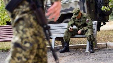 A Ukrainian soldier walks past a Russian serviceman in Soledar in the Donetsk region on Saturday as truce talks continued.