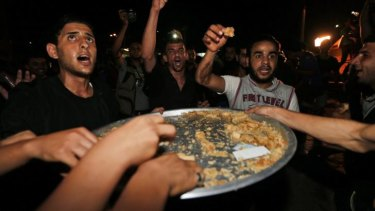 Palestinians celebrate with sweets outside the Shifa hospital in Gaza City following the reported capture of an Israeli soldier during fighting in the Gaza Strip.