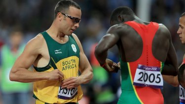 Mutual respect ... South Africa's 'Blade Runner' Oscar Pistorius exchanges numbers with world champion Kirani James after failing to qualify from the 400m semi-final.