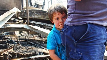 Devastation: Lyndon Dunlop stands by his father as they inspect the damage to his grandparent's Winmalee home of 41 years.
