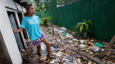 Nym stands in floodwater near her home in Bangkok.