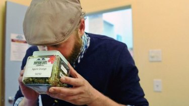 A Texan visitor smells a variety of marijuana called Agent Orange at the Northern Lights Cannabis Co in Edgewater near Denver.