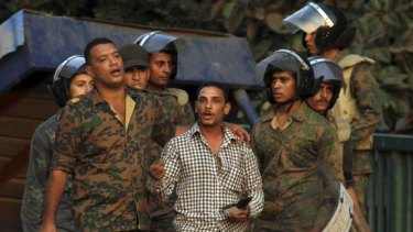 Night of violence: Egyptian soldiers detain a protester outside the Israeli embassy in Cairo.