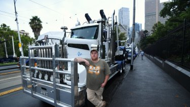 Logging trucks parked around state Parliament to protest the closure of the Heyfield Timber Mill.