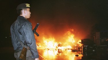 An Indonesian policeman, left, watches as cars burn in the street following a bomb explosion in front of a church in Jakarta on December 24, 2000.