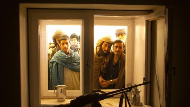 Afghans look through the window into the bedroom of Taliban leader Mullah Omar as they go through his compound on the outskirts of the Afghan city of Kandahar in 2001.