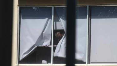 The alleged hostage taker looks through the window.