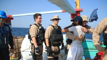 An American sailor greets a crew member of the Iranian-flagged dhow Al Molai after rescuing the fishing vessel from pirates in the Arabian Sea.