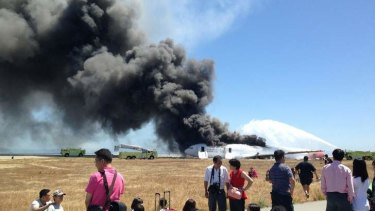 Evacuated passengers are seen on the tarmac as Asiana Airlines flight 214 burns on the runaway. Reports suggest not all were graceful under the great pressure of the evacuation.