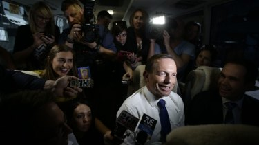 Potential winners are grinners: Tony Abbott joins a media bus group during his campaign visit to Brisbane, as an opinion poll brought good news for the Coalition.