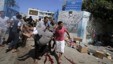Palestinians carry a wounded man after an Israeli air strike at a UN school in Rafah on Sunday.