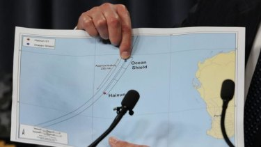 Retired Air Chief Marshal Angus Houston points to a graphic of the search area for the missing jet.