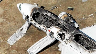 The Asiana Airlines airplane lies burned near the runway after it crash-landed at San Francisco International Airport on July 6.