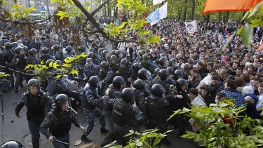 Russian riot police scuffle with protesters.