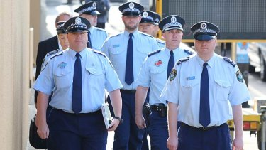 Police officers arrive at the Coroner's Court for the  inquest into the death of Roberto Laudisio Curti.