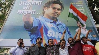 National hero: Cricket fans in front of a billboard of cricketer Sachin Tendulkar outside a stadium in Mumbai.