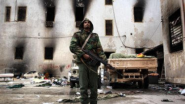 An opposition militiaman stands guard in front of the charred national security building in Libya's second city, Benghazi.