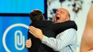 icrosoft CEO Steve Ballmer hugs host Ryan Seacrest.