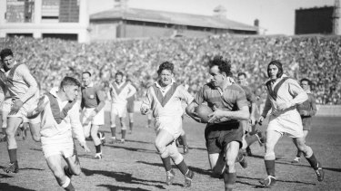 Old school: Clive Churchill weaving his magic for the Rabbitohs against the Dragons at the SCG in 1953.
