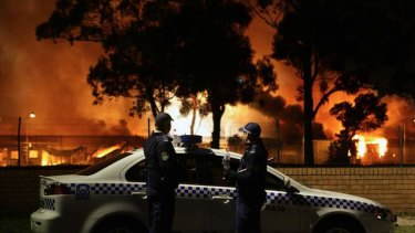 Police look on as several buildings burn during the Villawood riots in 2011.