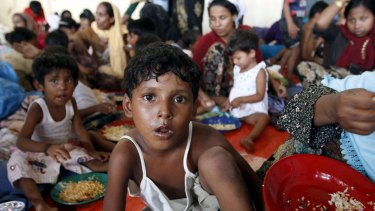 A young Rohingya migrant, who arrived in Indonesia today by boat with other Rohingya and Bangladeshi migrants, eats inside a temporary shelter at Kuala Langsa in Indonesia's Aceh Province.