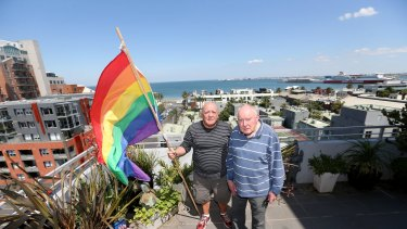 James Bellia and Murray Sheldrick on the balcony of their Port Melbourne apartment, after being told to stop flying their flag.