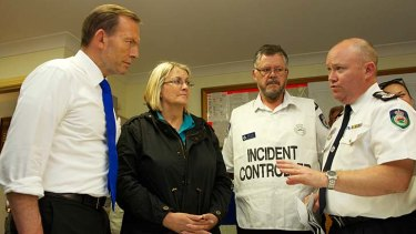 NSW RFS Commissioner Shane Fitzsimmons (far right) briefs Prime Minister Tony Abbott, Superintendent David Jones and local MP Louise Markus at Winmalee last week.