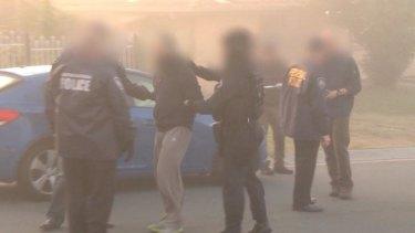 Australian Federal Police arrest a man during a raid on an Islamic store in Logan, south of Brisbane.