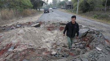 A Thai man walks though a crater left by an artillery shell.