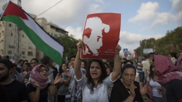A protester holds a portrait of Mohammad Abu Khadeir, the Palestinian boy who was kidnapped and killed.