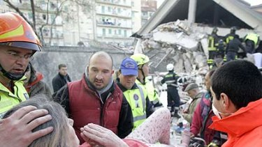 "A ""terrifying, bloody dawn''  . . . rescuers treat a woman injured in the earthquake that devastated the central Italian town of L'Aquila."