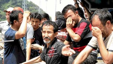 Asylum seekers from Afghanistan, Iraq and Iran cry as Indonesian officers force them to leave an Australian vessel.