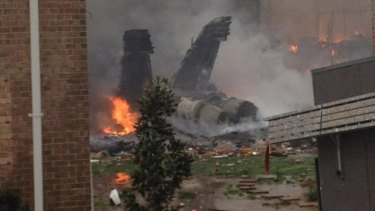 The burning fuselage of US Navy jet lies smoldering after crashing into a residential building.