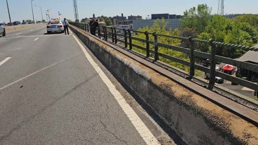 Skid marks and a scraped concrete barrier mark the spot where the van plunged off the road.