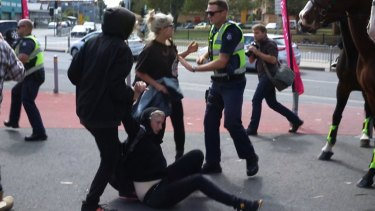Police attempt to calm clashing protesters outside the Halal festival in Ascot Vale.
