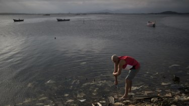 A man washes himself in the polluted waters of Guanabara Bay in the lead-up to the Rio Games.