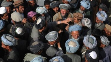 Landslide-affected Afghan villagers gather to receive donated supplies.