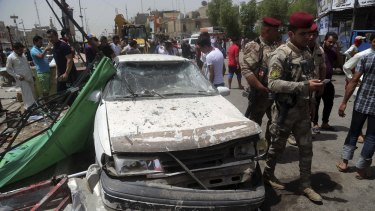 Security forces and citizens inspect the scene after a car bomb explosion at a crowded outdoor market in Sadr City.