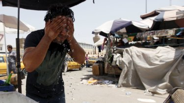 A man washes his face to cool off in Baghdad.