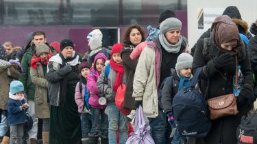 Refugees walk to a chartered train at the railway station of Passau, Germany Tuesday Jan. 2016. Migrants continue to arrive in Germany to seek for asylum.  (Armin Weigel/dpa via AP)
