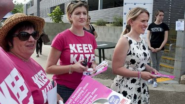 Labor's Kate Jones passes out how to vote cards outside The Gap State School.