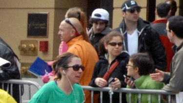 Faces in the crowd ... The Tsarnaev  brothers Tamerlan (in the black cap and Dzhokhar (in the white cap) looked like any other spectators at the Boston Marathon.