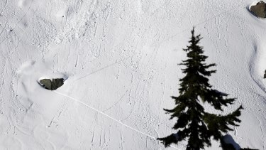 """In this January 11 photo, a pair of diagonal lines left by a skier cross dozens of lines left by """"roller balls,"""" are a warning sign of avalanche terrain."""