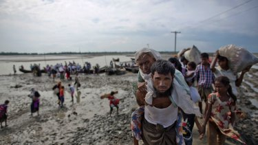 A Rohingya Muslim man from Myanmar carries an elderly woman after they crossed the border into Bangladesh from Myanmar, in Teknaf, Bangladesh.