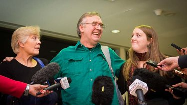 Greenpeace activist Colin Russell, with his wife Christine and daughter Madeleine, speaks to the media after arriving back in Hobart.
