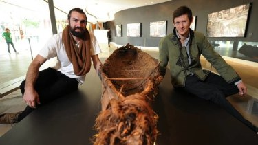 Indigenous artist Steaphan Paton and photographer Cameron Cope with a traditional canoe.