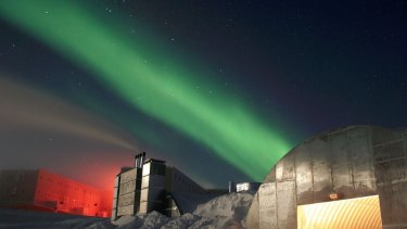 A photo of the station in the night under the glow of the aurora australis.