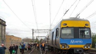 Passengers exit a train near Caulfield station after an overhead power line was cut.