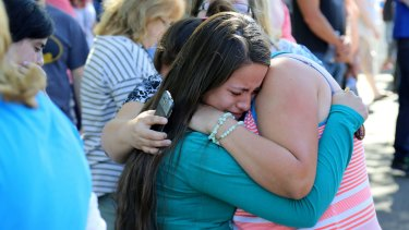 Grim toll: A woman is comforted after the shooting at Umpqua Community College.